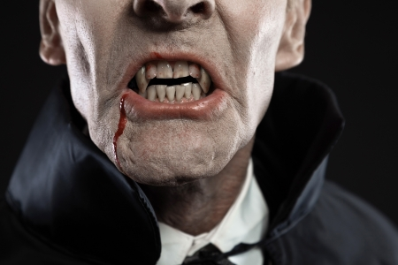 Close-up of dracula with black cape showing his scary teeth. Vamp fangs. Studio shot against black.
