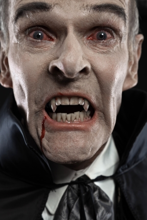 Dracula with black cape showing his scary teeth. Vamp fangs. Studio shot against black.