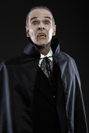 Dracula with black cape showing his scary teeth. Vamp fangs. Studio shot against black. photo