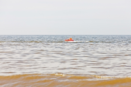 Kid in rubber ring going fast behind boat in ocean  Having fun in summertime  photo