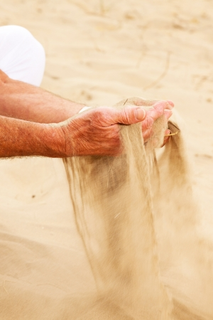Close-up of sand falling from senior mans hand. photo