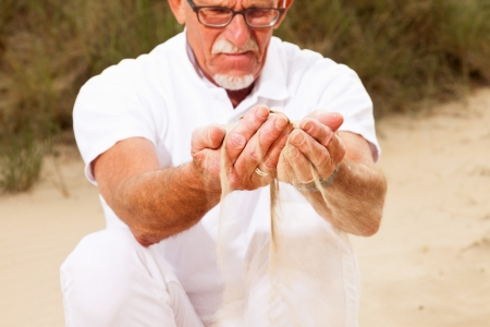 Retired senior man with sand falling from his hands. photo