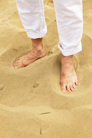 Feet of senior man standing in sand. Wearing white pants. photo