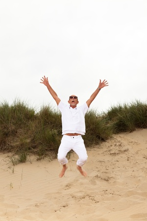 Jumping happy retired man with beard and sunglasses in grass dune landscape with cloudy sky. photo