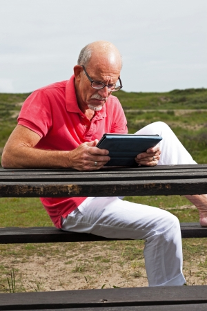 Retired senior man resting and using his tablet at table in park outdoors in grass dune landscape. photo