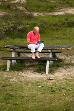 Retired senior man resting and using his tablet at table in park outdoors in grass dune landscape. Stock Photo - 21421527