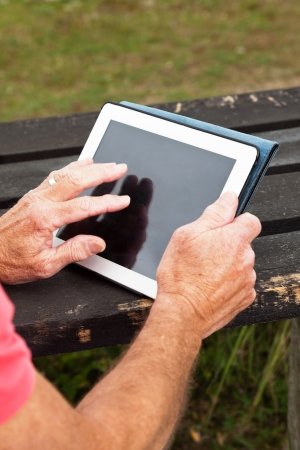 Close-up of hands of retired senior man resting and using his tablet at table in grass dune landscape. photo