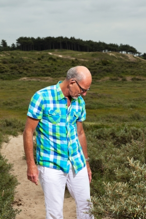 white pants: Retired senior man walking outdoors in grass dune landscape. Wearing white pants and green blocked shirt. Stock Photo