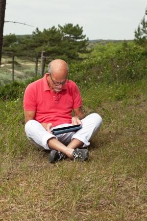 highlander: Hombre jubilado mayor que se sienta con la tableta al aire libre en una pradera. ESCOC�S vacas en el fondo.