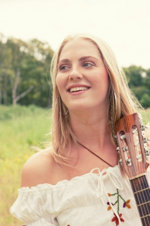 Retro blonde 70s hippie girl with acoustic guitar outdoor in nature. Standing in meadow. photo