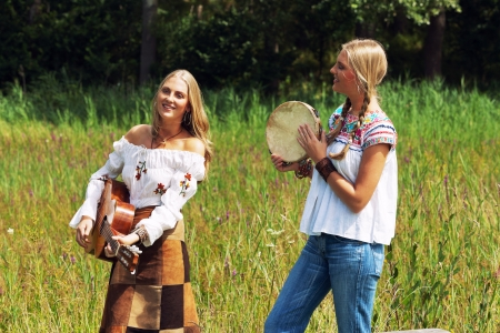 making music: Two retro blonde 70s hippie girls making music with acoustic guitar and tambourine outdoor in nature