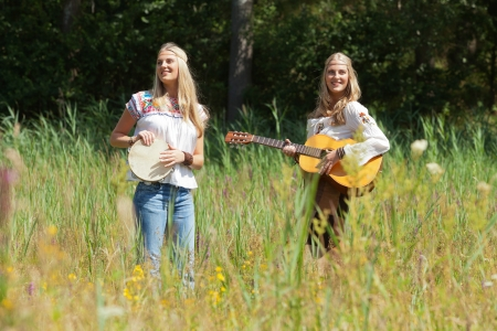 making music: Two retro blonde 70s hippie girls making music with acoustic guitar and tambourine outdoor in nature.