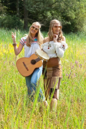 tambourine: Two retro blonde 70s hippie girls with sunglasses making music with acoustic guitar and tambourine outdoor in nature.