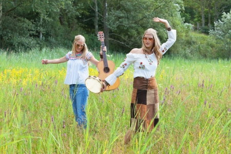 making music: Two retro blonde 70s hippie girls with sunglasses making music with acoustic guitar and tambourine outdoor in nature.