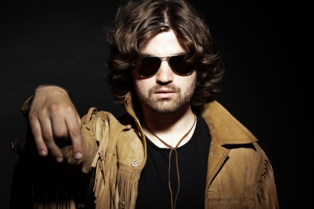 long hair boy: Cool rock style musician with long brown hair and beard. Holding a cigarette. Wearing sunglasses.
