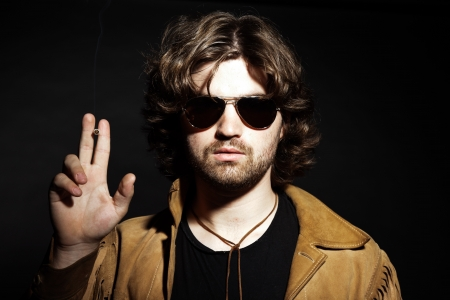 Cool rock style musician with long brown hair and beard. Holding a cigarette. Wearing sunglasses. photo
