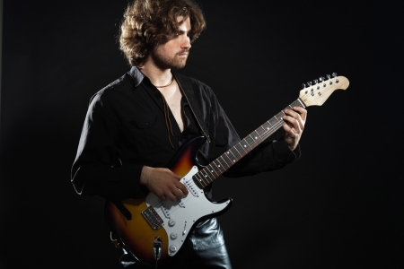 Psychedelic rock guitarist with long brown hair and beard. Dressed in black. photo