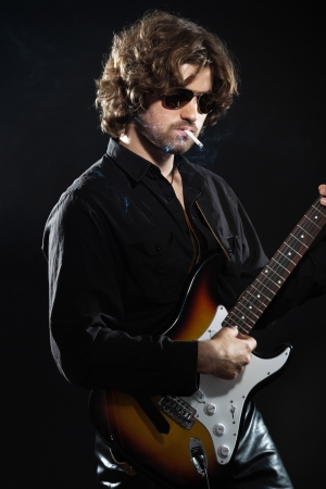 Psychedelic rock guitarist with long brown hair and beard. Dressed in black. Wearing sunglasses. photo