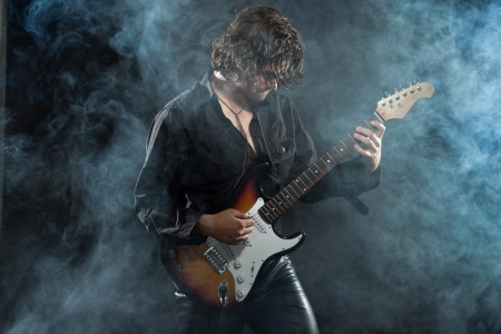 Psychedelic rock guitarist with long brown hair and beard. Dressed in black. Stage smoke. photo
