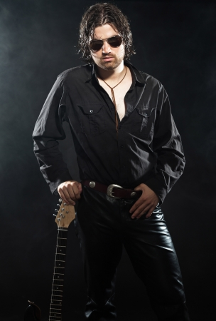 Rock guitarist with long brown hair and beard and sunglasses dressed in black. Rockstar performer. photo