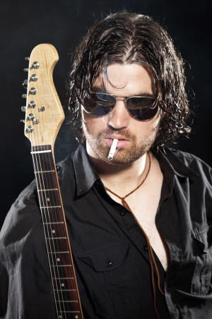 Rock guitarist with long brown hair and beard and sunglasses dressed in black. Smoking a cigarette. photo