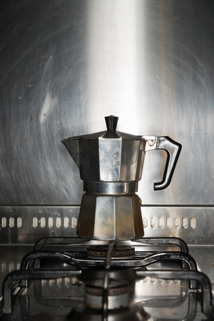 Classic metal espresso maker standing on cooker. photo