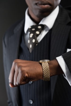 Retro african american gangster wearing striped suit and tie and black hat. Looking on his watch. Studio shot. photo