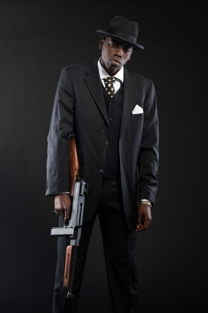 Retro african american mafia man wearing striped suit and tie and black hat. Holding machine gun. Studio shot. photo