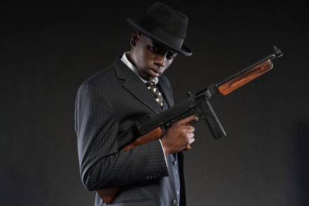 Retro african american mafia man wearing striped suit and tie and black hat. Holding machine gun. Studio shot. Reklamní fotografie