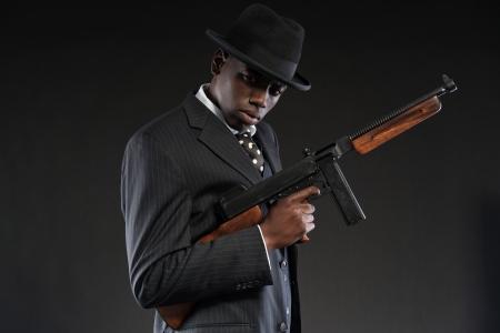 Retro Afrikaanse Amerikaanse mafia man draagt gestreepte pak en stropdas en zwarte hoed. Houden machinegeweer. Studio-opname. Stockfoto