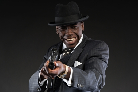 Retro african american mafia man wearing striped suit and tie and black hat. Shooting with machine gun. Studio shot. photo
