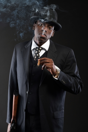 Retro african american mafia man wearing striped suit and tie and black hat. Smoking cigar. Holding a gun. Studio shot. photo