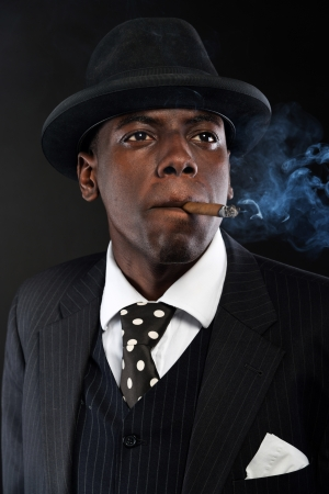 Retro african american mafia man wearing striped suit and tie and black hat. Smoking cigar. Studio shot. photo