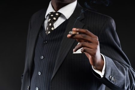 Close-up of hand of retro african american mafia man wearing striped suit and tie. Smoking cigar. Studio shot. photo