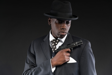 Retro african american mafia man wearing striped suit and tie and black hat. Holding a gun. Studio shot. photo