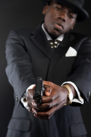 Retro african american mafia man wearing striped suit and tie and black hat. Shooting a with gun. Studio shot. photo