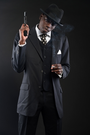 Retro african american mafia man wearing striped suit and tie and black hat. Holding a gun. Smoking cigarette. Studio shot. photo