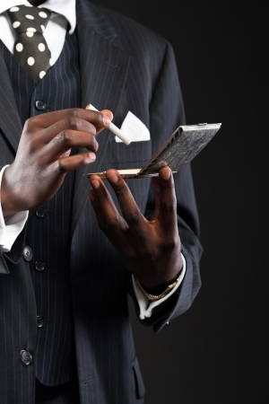 Close-up of hands of retro african american gangster man wearing striped suit and tie. Taking cigarette out of silver box. Studio shot. photo