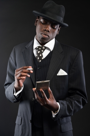 Retro african american gangster man wearing striped suit and tie and black hat. Taking cigarette out of silver box. Studio shot. photo