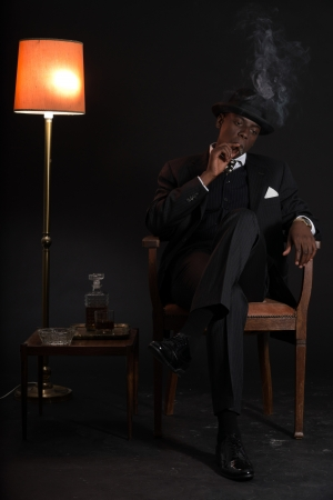 Retro african american gangster man wearing striped suit and tie and black hat. Sitting in a chair in living room. Smoking cigar. photo