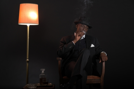 Retro african american gangster man wearing striped suit and tie and black hat. Sitting in a chair in living room. Smoking cigar. Stock Photo - 22473108