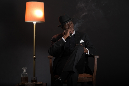 Retro african american gangster man wearing striped suit and tie and black hat. Sitting in a chair in living room. Smoking cigar. Stock Photo - 22473153