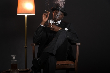 Retro african american gangster man wearing striped suit and tie and black hat. Sitting in a chair in living room. Smoking cigar. Holding glass of whisky. photo