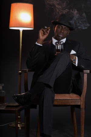 Retro african american gangster man wearing striped suit and tie and black hat. Sitting in a chair in living room. Smoking cigar. Holding glass of whisky. Stock Photo