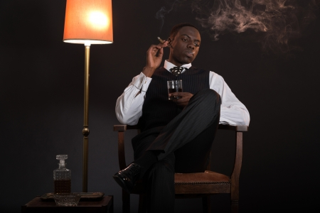 Retro african american gangster man wearing striped suit and tie. Sitting in a chair in living room. Smoking cigar. Holding glass of whisky. photo