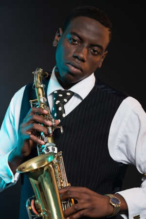 african sax: Retro african american jazz musician holding his saxophone. Wearing suit and tie. Studio shot.