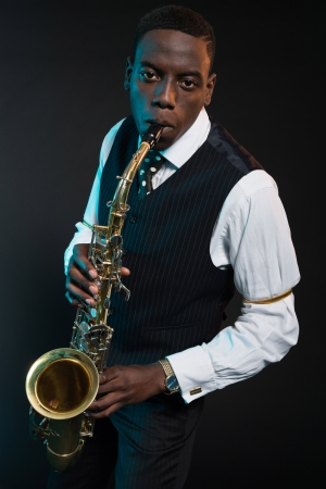 african sax: Retro african american jazz musician playing on his saxophone. Wearing suit and tie. Studio shot.