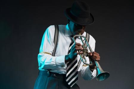 レトロなアフリカ系アメリカ人ジャズ音楽家彼のトランペットを演奏します。シャツとネクタイと帽子身に着けています。スタジオ ショットします
