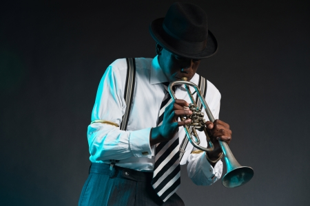 Retro african american jazz musician playing on his trumpet. Wearing shirt and tie and hat. Studio shot. Standard-Bild