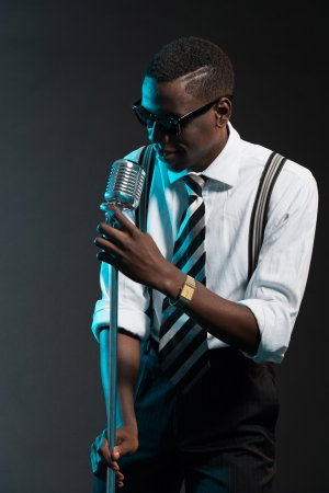 Retro african american jazz singer with microphone. Wearing shirt and tie and sunglasses. Studio shot. Stok Fotoğraf